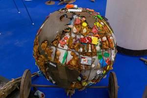 Kritisches Kunstobjekt Weltkugel aus Metall mit Kontinenten und Müll in den Ozeanen