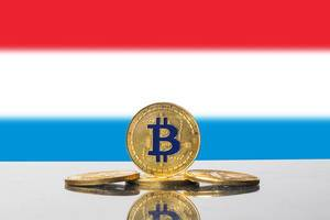 Kryptowährung Bitcoin als goldene Münzen vor der Flagge von Luxemburg