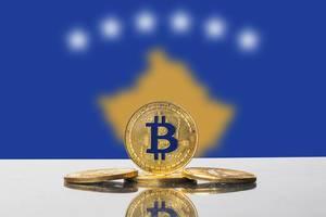 Kryptowährung Bitcoin in Form von Münzen arrangiert vor der Flagge des Kosovo