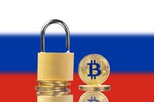 Kryptowährung Bitcoin und Vorhängeschloss mit der Flagge Russlands im Hintergrund