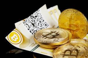 Kryptowährung: Goldene Bitcoins und Scheine vor schwarzem Hintergrund