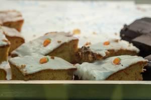 Kuchen mit weißer Zuckerglasur und kleinen Karotten aus Fondant oben drauf