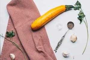 Küchen-Motiv: gelbe Zucchini, Knoblauch und Kräuter