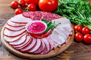 Küchenbrettchen mit aufgeschnittenen geräucherten Wurstwaren, Salami und Schinken mit pinker Sauce auf Holztisch