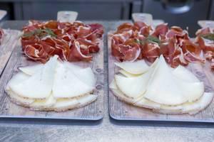 Küchenbretter mit dünnen Scheibchen von Käse und Rohschinken