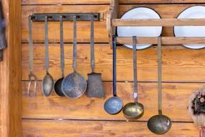 Küchenutensilien aus Metall hängen an einer Holzwand