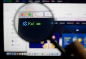 KuCoin-Logo am PC-Monitor, durch eine Lupe fotografiert