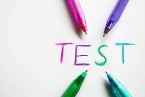 Kugelschreiber verschiedener Farben zeigen auf das Wort TEST