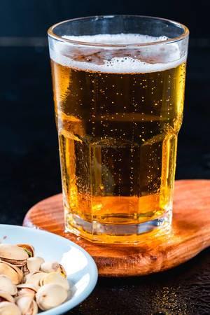 Kühles Bier in Glas mit Schale mit gesalzenen, ungeschälten Pistazien
