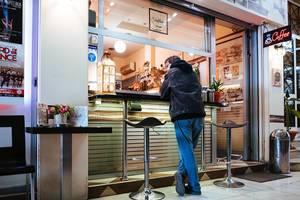 Kunde kauft griechisches Streetfood an einem Imbiss mit beleuchteter Theke, in Athen - Griechenland