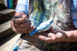 Künstler bemalt Vogel aus Keramik