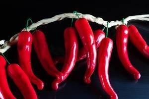 Künstliche Peperoni-Chilischoten, aufgehängt vor schwarzem Hintergrund