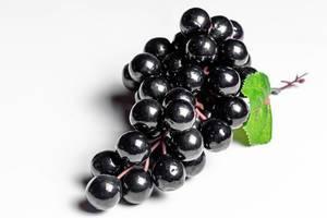 Künstliche Schwarze Weintrauben auf weißem Hintergrund Nahaufnahme
