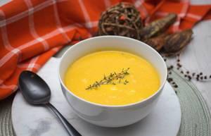 Kürbis-Creme-Suppe in einer Schüssel mit einem Zweig Thymian