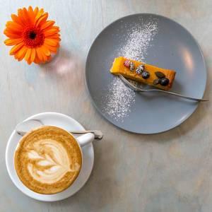 Kürbiskuchen auf einem Teller und eine Tasse Cappuccino mit einer Blume in der Aufsict
