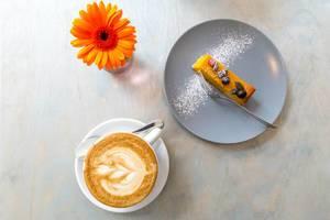 Kürbiskuchen mit Kernen und Puderzucker verziert auf einem grauen Teller mit einer Tasse Cappuccino und einer orangenen Gerbera