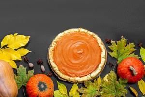 Kürbisse mit gelben Blättern und einem Kürbiskuchen als Hintergrund für Thanksgiving