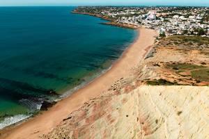 Küste bei Reserva da Luz, Portugal mit Klippen, Sandstrand, blauem Meer und weißer Stadt im Hintergrund