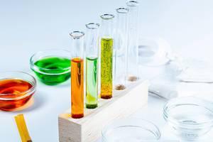 Labor-Analyse Konzeptbild mit Reagenzgläsern mit Flüssigkeit in einem Holzständer, Glasschalen, Schutzbrille und Indikator-Teststreifen zur pH-Wert Analyse vor weißem Hintergrund