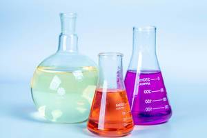Laboratory glassware with colored liquids on light background (Flip 2020)