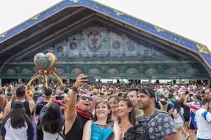 Lachende Besucher machen ein Selfie beim Eingang des Tomorrowland Festivals