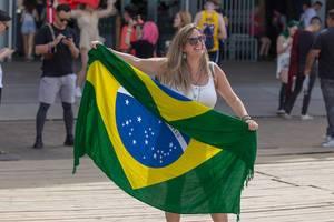 Lachende Festivalbesucherin am Tomorrowland 2019 hält Flagge von Brasilien