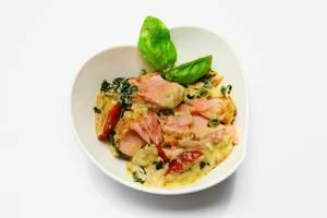 Lachs-Käse-Salat mit Gemüse und Basilikumblättern auf dekorativem Teller