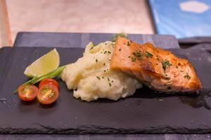 Lachsfilet mit Kartoffelstock, Tomaten und Limette auf Steinplatte serviert