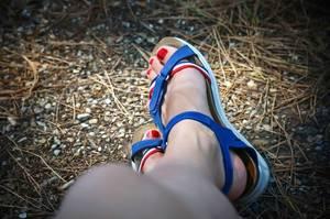 Lackierte Fußnägel in Sandalen