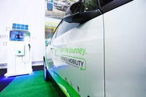"""Ladestation für E-Auto und weißes Auto mit Beschriftung """"Electrify your life journey"""" von Engie E-Mobility"""