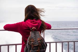 Lady in red pullover with backpack on her back looking out into the sea while the wind blows her hair (Flip 2019)