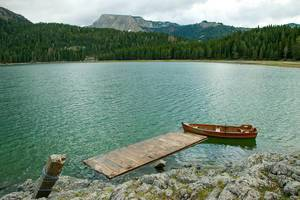 Landscape Photo of Wooden Rowing Boat in a Lake with Forest and Mountains in the Background at Durmitor National Park in Montenegro