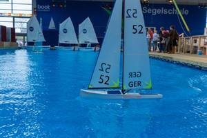 Large indoor pool with miniature sailboats promotes sailing school at exhibition boot Düsseldorf