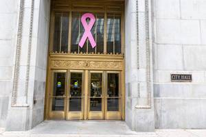Large pink ribbon for breast cancer awareness at the entrance of the City Hall in Chicago