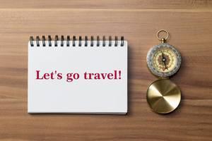 Lass uns verreisen - Ein Kompass mit einer Aufschrift auf einem Notizblock  - Lets go travel