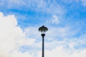 Laternenmast mit bewölktem Himmel im Hintergrund