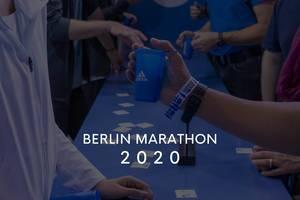 """Läufer am Adidas-Stand mit Getränkebechern und dem Bildtitel """"Berlin Marathon 2020"""""""
