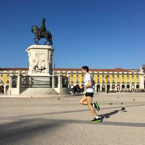 Läufer am Praça do Comércio Platz mit der Reiterstatue (Joseph I) im Hintergrund - Lissabon, Portugal