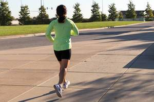 Läuferin in schwarz-grüner Sportbekleidung