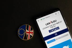 Leave.eu Website auf dem Handy-Display mit Brexit-Symbolik auf Metalmünze