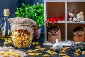 Lebensmittel-Hintergrundbild aus der Küche, mit Gewürzen, Öl, Chili, Knoblauch und Nudeln