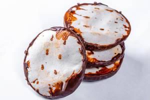 Lebkuchen-Taler mit weißer und dunkler Schokolade vor weißem Hintergrund