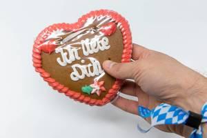 Lebkuchenherz vom Oktoberfest mit der Schrift - Ich Liebe Dich - gehalten von einer Hand