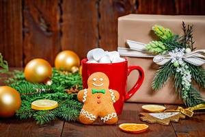 Lebkuchenmann an roter Tasse mit Marshmallows und Tannenzweigen und Geschenk im Hintergrund