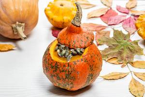 Leckerer Halloween Kürbis mit Kürbiskernen auf einem weißen Holzhintergrund mit gelben Blättern