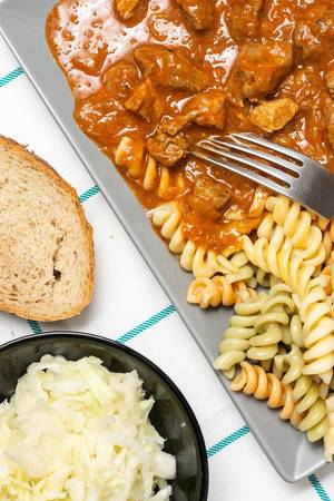 Leckeres Gulasch mit Pasta, Krautsalat und Stück frischem Brot auf Tisch