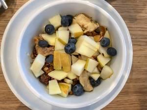 Leckeres Müsli zum Frühstück mit Blaubeeren, Birnen und Trockenobst in weißer Schüssel auf Holztisch