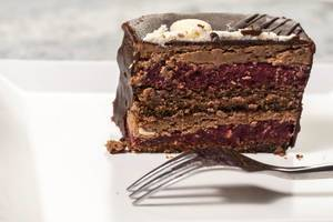 Leckeres Stück Schokoladenkuchen mit Kirschen und Schokoladenglasur auf Dessertteller
