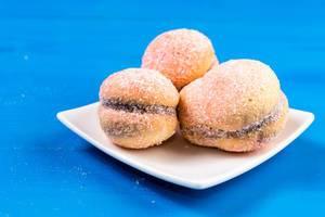 Leckeres Zuckergebäck auf weißem Teller auf blauem Holztisch