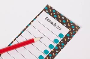 Leere Einkaufsliste auf buntem Notizblock mit Bleistift auf weißem Tisch